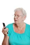 Mujer mayor que intenta utilizar un teléfono celular Fotos de archivo