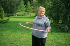 Mujer mayor que juega con su aro Foto de archivo libre de regalías