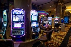 Mujer mayor que juega las máquinas tragaperras en el casino de Las Vegas imagenes de archivo