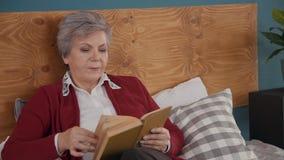 Mujer mayor que lee el buen libro en casa metrajes