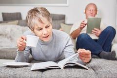 Mujer mayor que lee un libro Imagenes de archivo