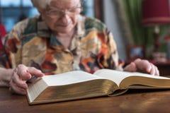 Mujer mayor que lee un libro Foto de archivo libre de regalías