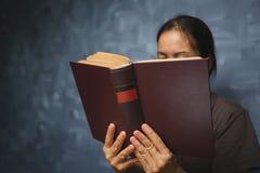 Mujer mayor que lee un libro en la sala de estar con el viejo tabl del vintage Foto de archivo