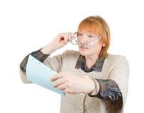 Mujer mayor que lee un papel imagen de archivo