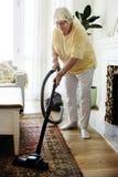Mujer mayor que limpia una alfombra con la aspiradora fotos de archivo