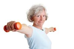 Mujer mayor que lleva a cabo dos pesas de gimnasia Fotos de archivo