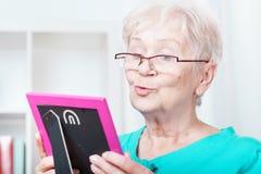 Mujer mayor que lleva a cabo el marco Fotografía de archivo libre de regalías