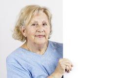 Mujer mayor que lleva a cabo la muestra en blanco Imagen de archivo libre de regalías