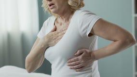 Mujer mayor que lleva a cabo las manos contra pecho, problemas con el corazón, vida agotadora almacen de metraje de vídeo