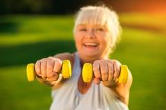 Mujer mayor que lleva a cabo pesas de gimnasia Fotografía de archivo