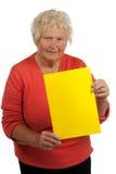 Mujer mayor que lleva a cabo a una tarjeta en blanco Fotos de archivo libres de regalías