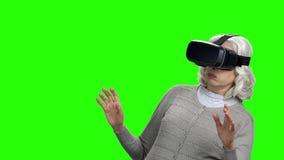 Mujer mayor que lleva los vidrios de la realidad virtual almacen de metraje de vídeo