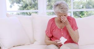 Mujer mayor que llora en el sofá almacen de metraje de vídeo