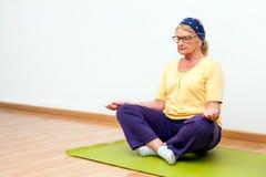 Mujer mayor que medita en gimnasio Fotografía de archivo libre de regalías