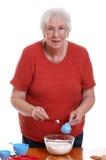 Mujer mayor que mide mientras que cuece al horno Imagenes de archivo