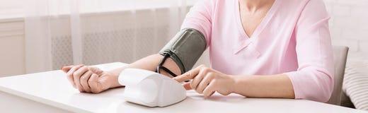 Mujer mayor que mide su presión arterial en casa imágenes de archivo libres de regalías