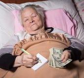 Mujer mayor que miente en cama Foto de archivo libre de regalías