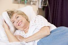 Mujer mayor que miente en cama de hospital Foto de archivo libre de regalías