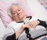 Mujer mayor que miente en cama y que sostiene efectivo del dólar Imagenes de archivo