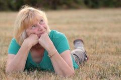 Mujer mayor que miente en la hierba que mira para arriba Foto de archivo