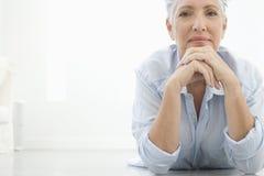 Mujer mayor que miente en piso Imagen de archivo libre de regalías
