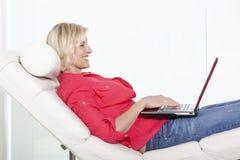 Mujer mayor que miente en silla con el ordenador portátil Fotografía de archivo libre de regalías