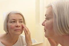Mujer mayor que mira el espejo de las arrugas foto de archivo