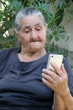 Mujer mayor que mira en un smartphone fotos de archivo libres de regalías
