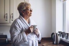 Mujer mayor que mira hacia fuera la ventana Fotos de archivo libres de regalías