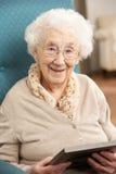 Mujer mayor que mira la fotografía en marco imágenes de archivo libres de regalías