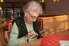 Mujer mayor que mira la pantalla de la tableta imagenes de archivo