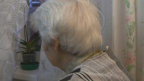 Mujer mayor que mira a la ventana metrajes