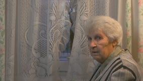Mujer mayor que mira a la ventana almacen de metraje de vídeo