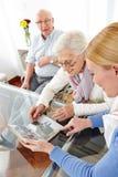 Mujer mayor que mira las fotos imagen de archivo