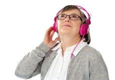 Mujer mayor que mira para arriba, perdido en mundo musical Imagen de archivo