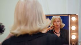 Mujer mayor que mira para duplicar mientras que hairstyling en estudio de la belleza Peluquero que peina el pelo con hairstyling  metrajes