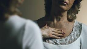 Mujer mayor que mira su reflexión, trastorno con el envejecimiento y la piel de la comba metrajes