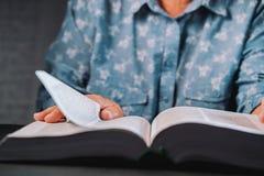 Mujer mayor que mueve de un tirón a través de las páginas del libro Abuela con la biblia Pensionista mayor concentrado con las ar fotos de archivo libres de regalías