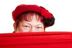 Mujer mayor que oculta detrás de la bufanda Fotos de archivo