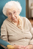 Mujer mayor que parece triste en silla Fotos de archivo