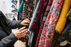 Mujer mayor que pasa a través de la ropa en tienda de la caridad del ahorro de la segunda mano, detalle en sus manos móviles foto de archivo