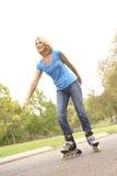 Mujer mayor que patina en parque Imágenes de archivo libres de regalías