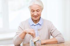 Mujer mayor que pone el dinero en el tarro de cristal en casa Foto de archivo libre de regalías