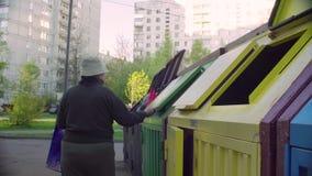 Mujer mayor que pone la basura en un compartimiento de la colección separada almacen de metraje de vídeo