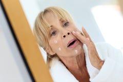 Mujer mayor que pone la crema antienvejecedora fotos de archivo