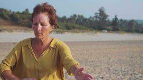 Mujer mayor que practica al aire libre gimnástico del taiji en la cámara lenta almacen de metraje de vídeo