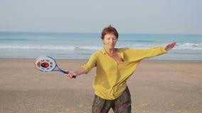 Mujer mayor que practica la bola del globo de la ji del tai en la playa metrajes