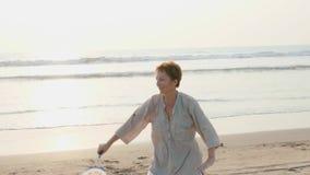 Mujer mayor que practica la bola del globo de la ji del tai en la playa en la puesta del sol almacen de video
