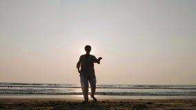 Mujer mayor que practica la bola del globo de la ji del tai en la playa en la puesta del sol metrajes