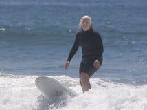 Mujer mayor que practica surf Imágenes de archivo libres de regalías